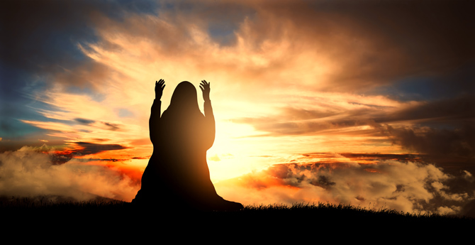 Betende Muslima beim Sonnenuntergang