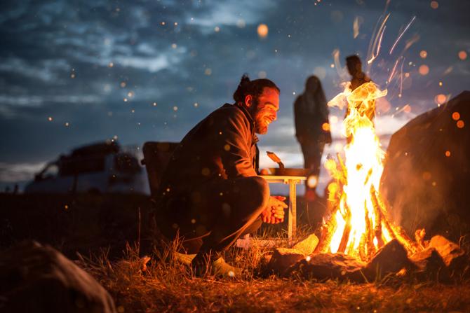 Mann vor loderndem Lagerfeuer